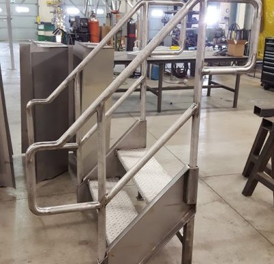 custom build metal steps and railing sitting on concrete floor in warehouse setting