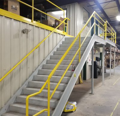 grey steel steps and yellow metal railing leading from factory floor to mezzanine