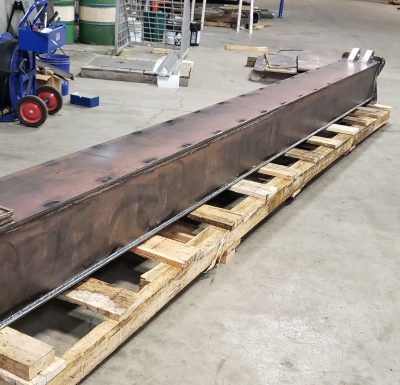 large metal rectangular object sitting on wood skid in warehouse setting beside forklift