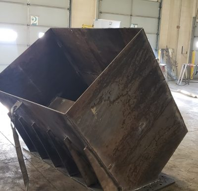 custom fabricated metal box sitting on concrete floor in front of large garage doors