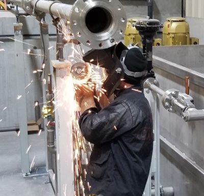 stoner industrial employee wearing protective gear using hand grinder on metal part in warehouse setting