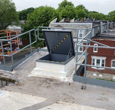 custom fabricated roof hatch sitting between metal railing overlooking row homes