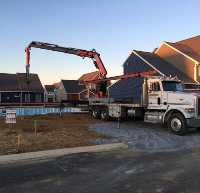 mobile crane truck parked on stone and dirt surface next to newly built residential units