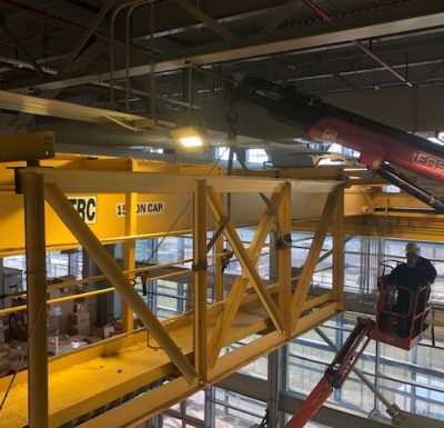 overhead crane assisting with work inside a warehouse environment