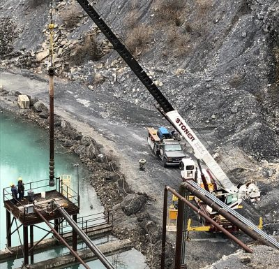 white colored mobile crane assisting workers install pipe over body of water