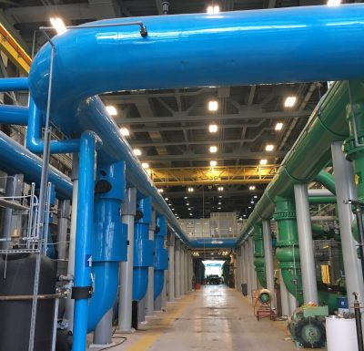 industrial facility with blue and green piping beneath fluorescent lighting