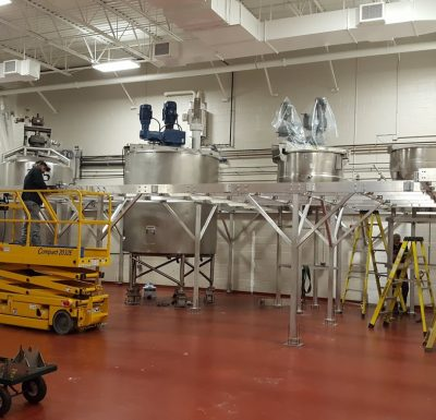 aluminum mezzanine being installed by craftsman standing on a yellow hydraulic lift