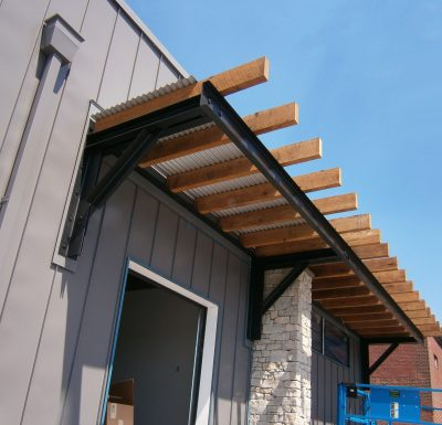 metal beams holding up wood two by fours on top of building with grey siding