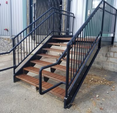 black metal railing leading down from green entrance door on to asphalt surface