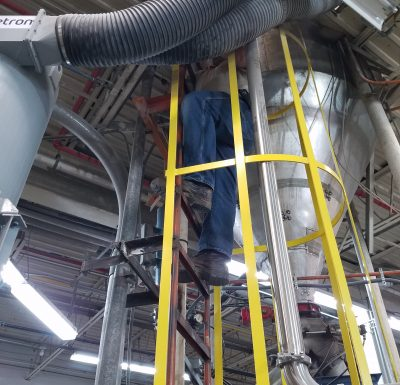 technician climbing ladder surrounded by yellow metal protective rails