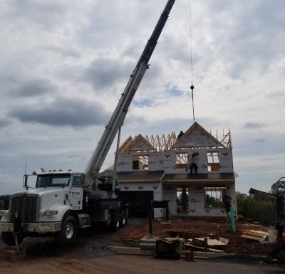 peterbilt mobile crane parked in front of newly built home under construction