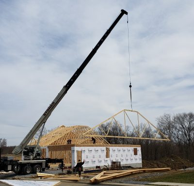 peterbilt mobile crane holding a piece of a newly built home in the air over job site