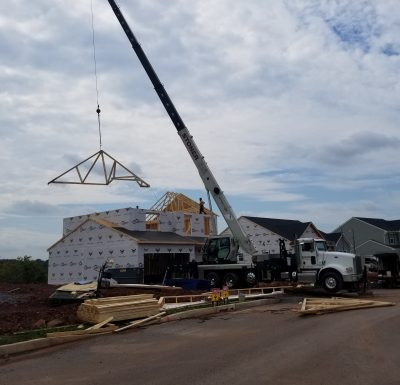 mobile crane holding piece of newly built homes roof while workers guide it into place