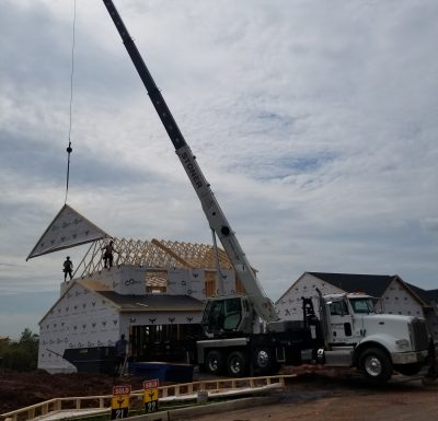 new home being built with the assistance of a mobile crane